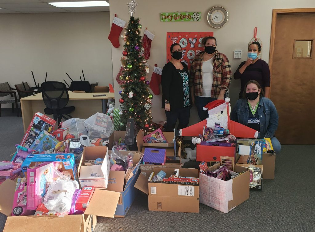 group of happy people in office with toys for tots donations