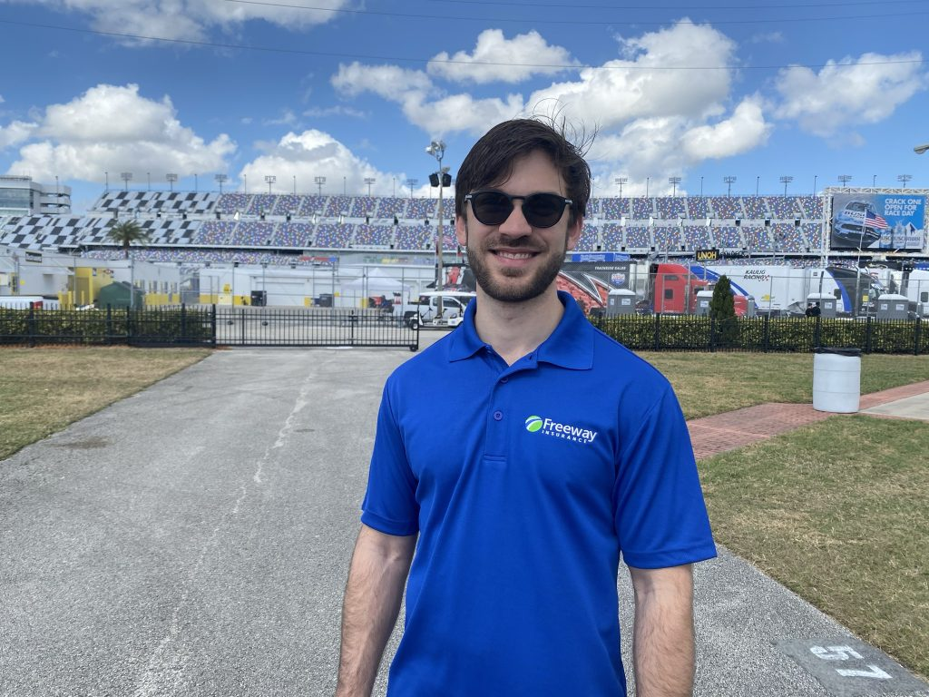 Race car driver Daniel Suarez wearing Freeway shirt standing outside of race track stadium